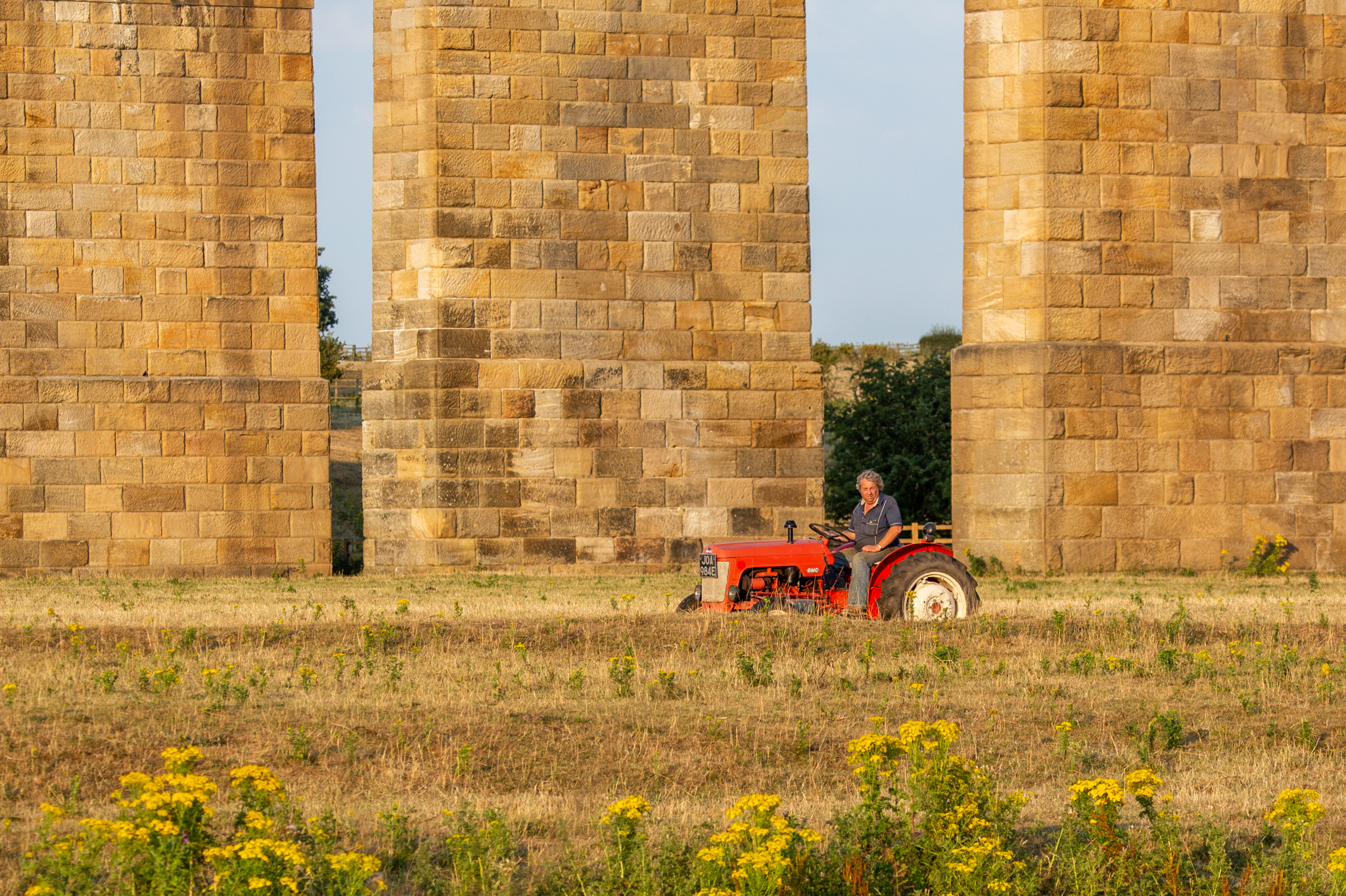 red Tractor with Farmer driving under bridge